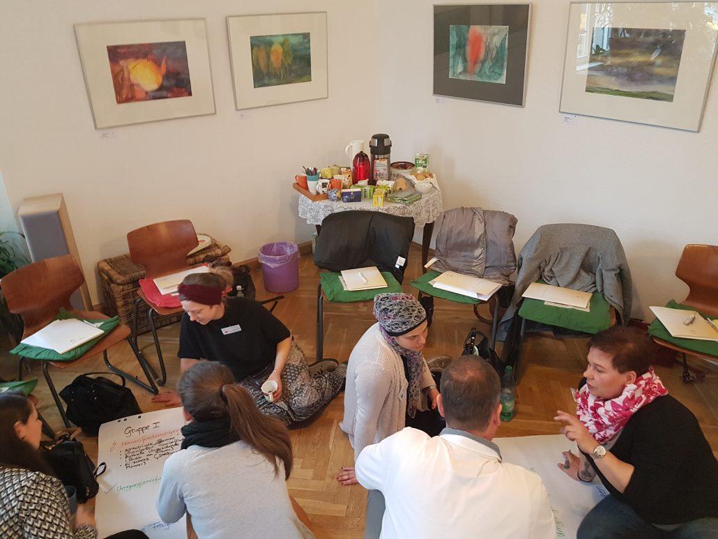 Teilnehmende arbeiten in Gruppen auf Flipcharts.